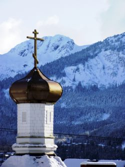onion dome of St. Nicholas in the winter. a Snow covered Douglas Island is in the background. I